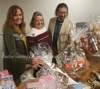 From left, Kimberly Reamer, executive director; Linda Thoma, director of operations and John Righetti, major gift officer, look over gift baskets ahead of the Nov. 2 Signature Sensations fundraiser for the Jean B. Purvis Health Center. ERIC FREEHLING/EAGLE PHOTO