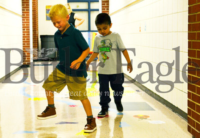 Elijah Jalpa, 5, and Dominic Adams, 5, try ou McQuistion Elementary's new hallway sensory walk. Tanner Cole/Butler Eagle