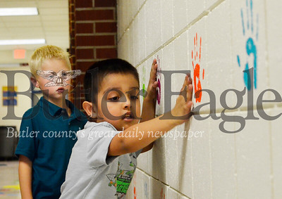Dominic Adams, 5, and Elijah Jalpa, 5,  try out McQuistion Elementary's new hallway sensory walk. The pair learned how to do wall-push ups during their first day of school Tuesday. Tanner Cole/Butler Eagle