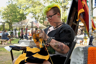 Cabot native Hannah Limbaugh knits a new scarf at her stand at Saxonburg Festival for the Arts Saturday. Limbaughs works featured quirky pop culture designs including a blanket designed to look like an 80s era Nintendo controller along with a host of knit caps with animals and other themes. Saxonburg closed off streets and welcomed guests from across the region to the two-day festival. Seb Foltz/Butler Eagle