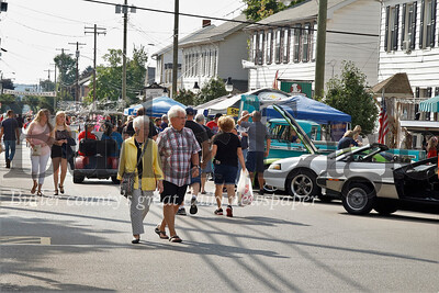 Saxonburg Festival of the Arts visitors stroll down Main St. looking at classic cars Saturday. The two-day festival features classic cars, arts and crafts, food and live music.  Seb Foltz/Butler Eagle