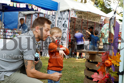Liam Hotkowski,2, points out some holliday-themed greeting signs that caught his eye. His father Leo Hotkowski (left) said he has fond memories of coming to the festival with his grandma as a kid and wanted to pass the tradition on to his son. Seb Foltz/Butler Eagle