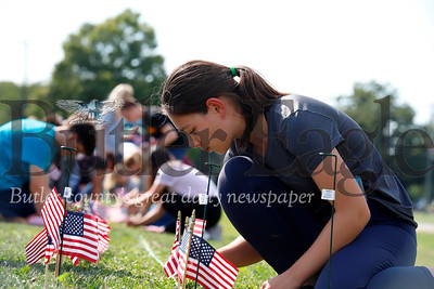 Leah Vainshtein places an American flag in the grass in front of Mars Senior High School. Seb Foltz/Butler Eagle