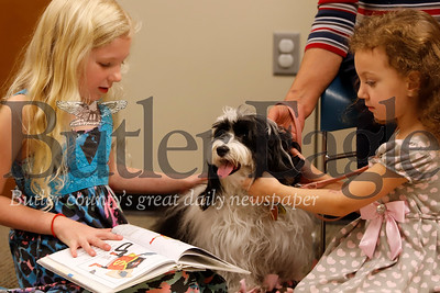 Gabriella, 7, and Madeline, 4, Parfitt read with one of the Paws-to-Read a Tale therapy dogs at the Butler Area Public Library Saturday. The event encourages young readers by giving them the opportunity to read with trained visitation dogs. The dogs in the program, part of the Butler Dog Training Association, also visit local hospitals and senior centers. Seb Foltz/Butler Eagle