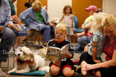 Vincent Greco,6, of Butler reads a story to Sprite, a trained visitation therapy dog from the Butler Dog Training Association, at the Butler Area Public Library Saturday, part of the library's Paws-to-Read a Tale program. The event builds confidence in young readers by encouraging them to read to the therapy dogs. Seb Foltz/Butler Eagle