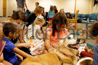 Amberlyn Roush reads a book with her son Aaron Griffin while daughter Serenity Griffin reads to Tucker the golden retriever at Butler County Library's Paws-to Read a Tale Saturday. The event encourages young readers to read with trained therapy visitation dogs. Seb Foltz/Butler Eagle
