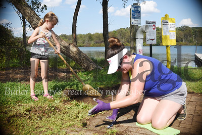 Tanni Mitchell and her six-year-old daughter Mitchell pick weeds out of a a brick path at Moraine State Park on Sunday. Tanner Cole/Butler Eagle