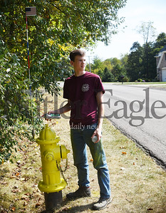 Jaxon Owens, 14, applies a clear coat finish to a fire hydrant in Jackson Township. Jaxon painted 93 fire hydrants as an Eagle Scout project. Tanner Cole/Butler Eagle