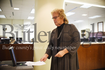 Shari Brewer, director the Butler County's election bureau, demonstrates how to submit a ballot into one of the county's new voting machines. The ballot shown is a fake demo ballot. Tanner Cole/Butler Eagle