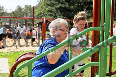 Betty Fitzgerald of the Butler Rotary paints a playground feature in Memorial Park. The Rotary hosted a volunteer day Saturday to rebuild and renovate the main playground in the park. Seb Foltz/Butler Eagle