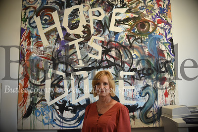 Tracy Hack stands with a Hope is Dope painting on display in her office. Recovering addicts in Butler's Hope is Dope group painted the art at an event in the Butler Art Center. Tanner Cole/Butler Eagle