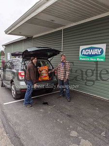 Ashley and John McDivitt, owners of the Saxonburg Agway store, load a bag of dog food into a customer's vehicle on Tuesday. The McDivitts are giving away free 40-pound bags of dog food during the coronavirus crisis until their supply runs out.