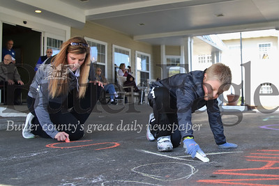 """Jonathan French, 7, and his mom Breanne French write a message in chalk to residents on lockdown at New Haven Court at Clearview senior center. The pair have also painted a message saying """"praying 4 your"""" on the front lawn. French and his mom have been spending the week writing messages to senior residents and first responders around the county this week. Seb Foltz/Butler Eagle"""