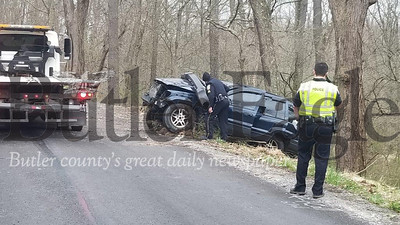 """Jim Smith photo. Police officers from Evans City-Seven Fields and Jackson Township inspect a damaged Jeep Grand Cherokee involved in a single-vehicle crash Tuesday morning on Pattison Street Extension in Jackson Township. A wrecker had to haul the Jeep out of a wooded area and up an embankment where it ended after the crash that police suspect happened during a """"rolling domestic."""" Two people, a former married couple, were injured."""