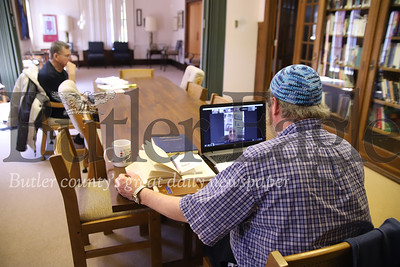 Congregation B'nai Abraham caretaker Ben Vincent leads his weekly bible study from his laptop with class member Karl Tamdurro sitting at the far end of the table practicing social distancing while the rest of the class follows through a Zoom video conference. Seb Foltz/Butler Eagle