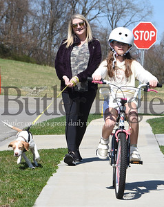 Harold Aughton/Butler Eagle: Delaney DiCuccio, 8, goes on bike ride with her mother, Jennifer, and the family's new pet, Jack, a rescue dog from the Butler County Humane Society, Monday, April 6, 2020.