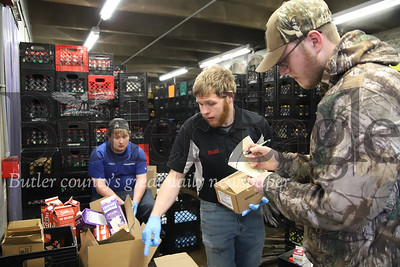 Frank Boring (left), Tyler Wilcox, and Dakota Ferguson package orders for curbside pickup at Marburger farm in Evan's City Thursday 04/09/20. With the COVID-19 outdbreak, the locally-based dairy farm has seen a significant loss in dairy sales forcing them to dump excess milk and adjust onsite pickup. Seb Foltz/Butler Eagle