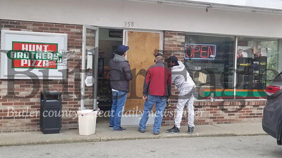 Jim Smith photo. Azeem Chatta (left), owner of the EZ Stop on North Main Street in Butler, along with his father and a friend help place plywood on the broken front glass door to his store, which city police say was burglarized shortly before 6:30 a.m. Sunday. Police arrested two Butler men in connection with the break-in and the theft of a safe.