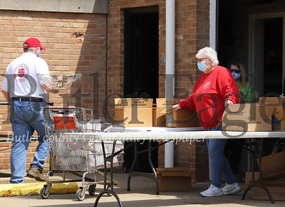 Captain Darlene Means and volunteers from the Butler Salvation Army hand out a meals from Operation BBQ Relief at a drive-thru pick up in downtown Bulter Saturday. The meals were provided by the nonprofit BBQ group which was created to respond in times of natural disasters and works in partnership with the Salvation Army and other organizations. Seb Foltz/Butler Eagle