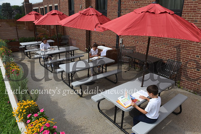 Harold Aughton/Butler Eagle: (left - right) Ava Roxberry, 12, 7th grader, Ruby Wissinger, 11, 6th grader, and John Fouse, 7, a 2nd grader at Butler Catholic try out the new outdoor classroom Tuesday morning.