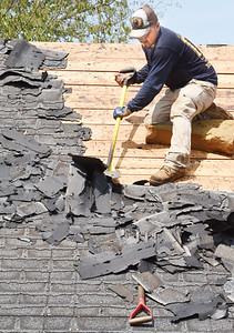 Harold Aughton/Butler Eagle: A roofer from G & Z roofing in Renfrew removes the shingles off a roof along Beacon Road in Penn Twp. Monday, August 10, 2020.