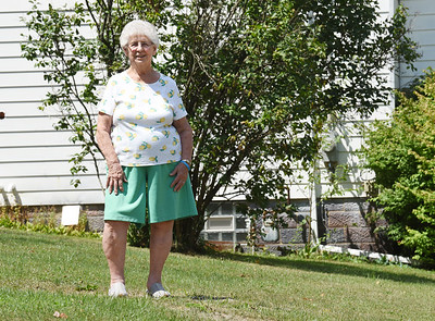 Harold Aughton/Butler Eagle: Florence DeBacco remembers the night when she housed 35 people in her home during a flash flood that claimed the lives of 9 people. The water nearly covered the cinder blocks of her basement behind her in the photo.