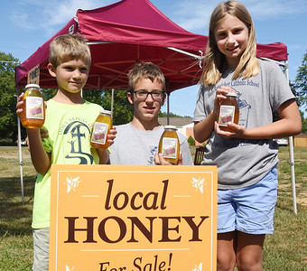 Harold Aughton/Butler Eagle: From left, siblings Carson, 7, Alex, 13, and Jeana, 9, Peglowski of Middlesex Twp. are selling local honey as a fundrasier for their school Holy Sepulcher. According to Alex, a local beekeeper was having trouble selling his honey due to COVID-19. So the beekeeper offered Alex and his siblings 50% of the profit if they would sell his honey. In just a few days the siblings sold 45 lbs of honey raising $270 for their school.