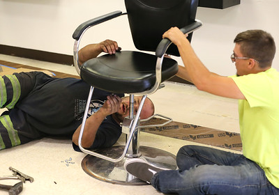 Ryan Wissinger (left) and Brendan Theisler fix a barber's chair at what will be the Encore Studio by Audra Jane salon in Moraine Point Point Plaza. Owner Audra Bowers is opening the salon and hiring all the laid of stylists from JC Penny's salon. Seb Foltz/Butler Eagle