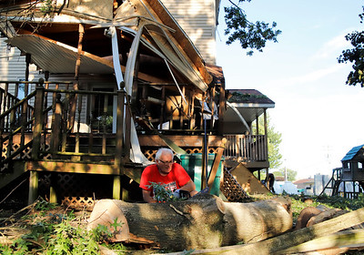 Jorn Jemsen cuts wood from a downed oak tree that damaged the porch of his daughter Kirsi Reesman's home on Main St. in Worthington. Witnesses said an intense microburst ripped through the town knocking over a number of trees and damaging property. Seb Foltz/Butler Eagle