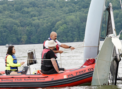 Harold Aughton/Butler Eagle: Members of the Moraine Sailing Club safety team secure a rope around a catamaran that capside during a learn to sail event Saturday, August 15, 2020.