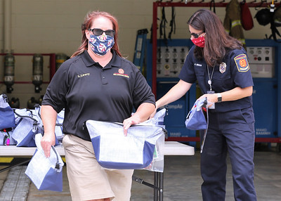 Cranberry police administrator Lori Lowry, fire and emergency service administrator Amy Behun and members of the Cranberry Township Community Response Team hand out bags of school supplies Thursday at the townthip's public works facility. Seb Foltz/Butler Eagle Aug. 27 Thurs