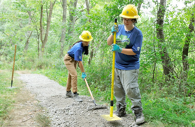Student Conservation Association trail crew members Brittni Strangis(right), 24, and Breanna Decaro, 22, spread gravel on the Hilltop Trail at Morraine State Park Wednesday. Seb Foltz/Butler Eagle Aug. 26 2020