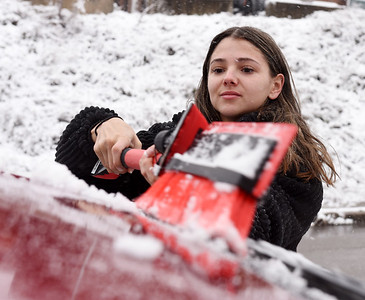Christina Sadler of Slippery Rock brushes the snow off of her car along S. Mckean Street in Butler Tuesday morning, December 1, 2020.  Harold Aughton/Butler Eagle