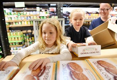 Emma Makowski, 7, received helps stocking shelves from her brother John, 3, and mother Erin Makowski, director of the Southwest Butler Food Cupboard, Wednesday, December 2, 2020. Harold Aughton/Butler Eagle.