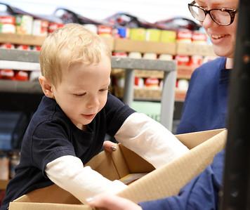 John Makowski, 3, helps his mother Erin Makowski, director of the Southwest Butler Food Cupboard, stock shelves Wednesday, December 2, 2020. Harold Aughton/Butler Eagle.