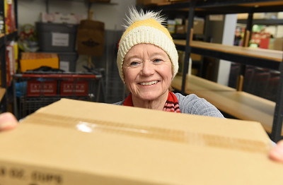 Phyllis Metz, treasurer for the Southwest Butler Food Cupboard, re-stocks the cupboard's shelves after a recent donation of food Wednesday, December 2, 2020. Harold Aughton/Butler Eagle.