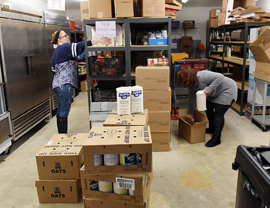 Erin Makowski, left, director of the Southwest Butler Food Cupboard, and volunteer Meg May of Zelienople stock shelves after the cupboard received a donation of food, Wednesday, December 2, 2020. Harold Aughton/Butler Eagle.