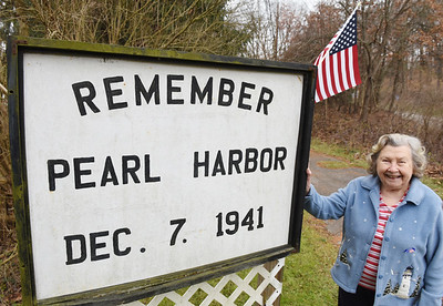 Majorie Mulvey, 91, of Jackson Twp. stands in front of the sign her late husband, WW II veteran Rosco Mulvey, made in rememberance of Pearl Harbor. Harold Aughton/Butler Eagle.