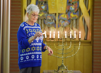 Shirley Grossman, 90, of Butler and a member of the B'nai Abraham Synagogue lights the menorah in preparation of Hanukkah, which begins at sundown Thursday. Harold Aughton/Butler Eagle