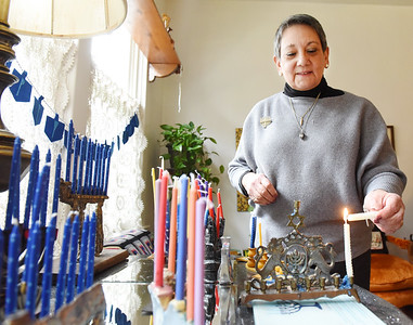 Roberta Gallagher of Butler lights the menorah her grandmother brought from Russia to Butler in the early 1900s Wednesday, December 09, 2020.  Gallagher is a member of the B'nai Abraham Synagogue and has 16 menorahs on a table in her living room in preparation to celebrate Hanukkah. Hanukkah begins at sun down Thursday. Harold Aughton/Butler Eagle
