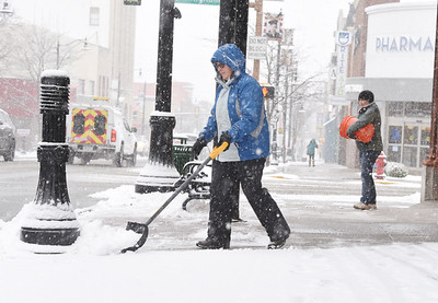 "Jackie Gray, left, and her sister-in-law, Kim Gray shovel and salt the sidewalks in front of the ""Cornerstone"" building at Cunningham and Main Street Wednesday afternoon, December 16, 2020. Harold Aughton/Butler Eagle"