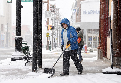 "Jackie Gray, left, and her sister-in-law, Kim Gray shovel and salt the sidewalks in front of the ""Cornerstone"" building at Cunningham and Main Street Wednesday afternoon, December 16, 2020."