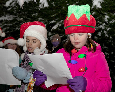 Evelyn Quinn,8,(right) and Penelope Cummings,8, join fellow members of Butler Girl Scout Troop 52938 and other carolers singing at Concordia Thursday. Around 60 or more volunteers spread some holiday cheer to residents watching and listening from their windows at the senior facility. Seb Foltz/Butler Eagle 12/17/20