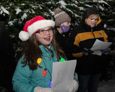 EDITORS NOTE: HOLD FOR LATER USE Kinsley Smith of Butler sings with carolers at Concordia Thursday. Smith's Girl Scout troop and around 60 carolers spread holiday cheer as senior residents at the facility watched and listened from their windows and porches. Seb Foltz/Butler Eagle 12/17/20