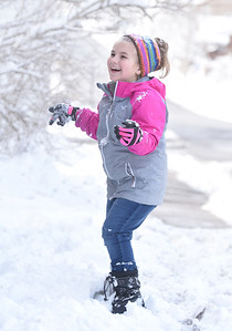 Lyric Sleigher, 9, of Butler plays in the snow while her great, grandfather James Snow, uses his snow blower to remove snow from the former Keep Sakes and Treasurers store front along West Wayne Street Thursday afternoon, December 17, 2020.