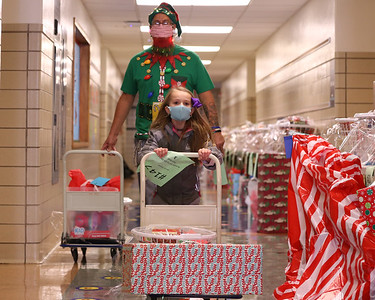Lexi Schnitgen,7, and Emily Brittain Elementary custodian Ray Gonzalez bring presents and food baskets out to a car at Saturday's Inspired Hearts and Hands drive-up holiday food and toy distribution at the elementary school. Seb Foltz/Butler Eagle 12/19/20