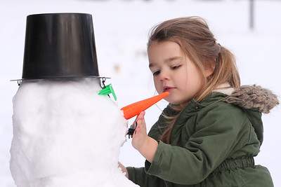 Evelina Coulter, 3, of Meridian adds a mouth to the family's backyard snowman Saturday. Seb Foltz/Butler Eagle 12/19/20