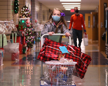 Lexi Schnitgen,7, pushes presents and food baskets out to a car at Saturday's Inspired Hearts and Hands drive-up holiday food and toy distribution at the Emily Brittain Elementary School. Seb Foltz/Butler Eagle 12/19/20