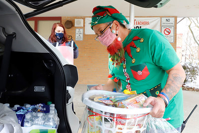 Emily Brittain Elementary custodian Ray Gonzalez brings presents and a food basket out to a car at Saturday's Inspired Hearts and Hands drive-up holiday food and toy distribution at the elementary school. Seb Foltz/Butler Eagle 12/19/20