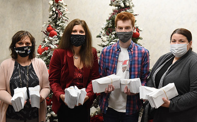 Armco Credit Union employees Miranda Lunn, and Michele Jurysta with Josh Riesmeyer of ANR and Hayley of CCR hold the gift cards to be distributed to local businesses Tuesday, December 22, 2020. Harold Aughton/Butler Eagle
